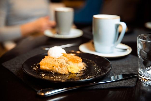 Knuspriges gebäckdessert neben einer tasse kaffee