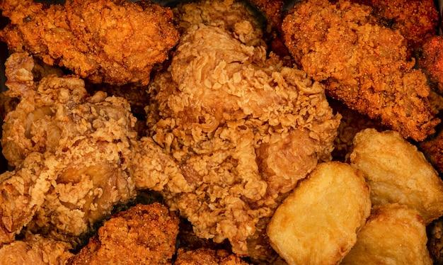 Knuspriges gebratenes huhn und nuggets. fast-food-hintergrund. würzig verspielt
