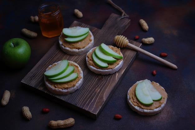 Knuspriges natürliches erdnussbuttersandwich mit reiskuchenbrot und grünen apfelscheiben und honig.