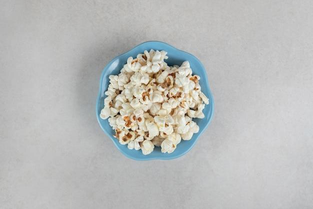 Knuspriges popcorn in einer kleinen blauen schüssel auf marmor.