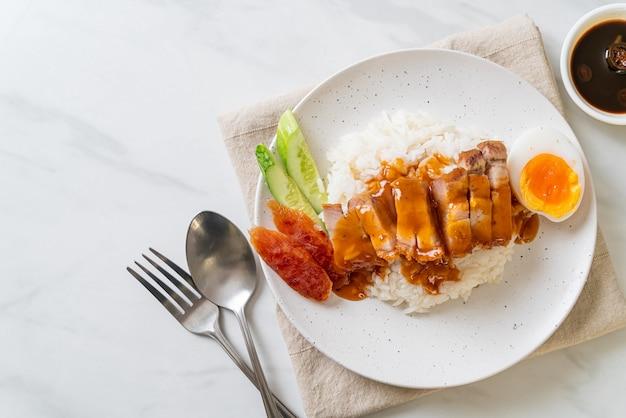 Knuspriges schweinebauch auf reis mit roter barbecue-sauce