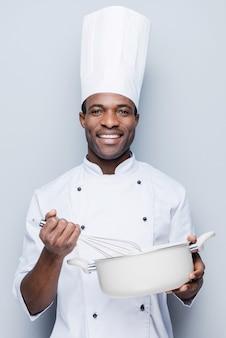 Koch bei der arbeit. fröhlicher junger afrikanischer koch in weißer uniform, der etwas in auflauf mischt