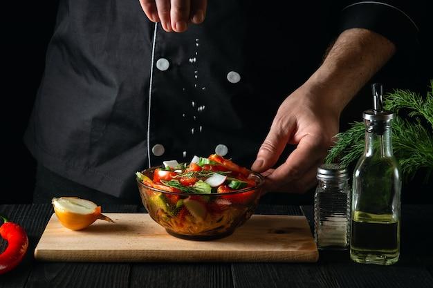 Koch besprüht gesalzenen frischen gemüsesalat in einem teller auf einem holztisch