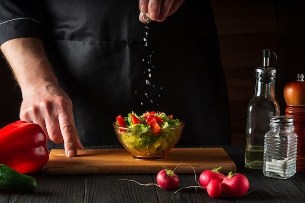Koch besprüht salzsalat mit frischem gemüse auf einem holztisch
