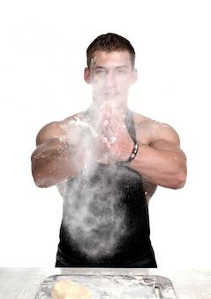 Koch bodybuilder klatscht in die hände mit mehl.