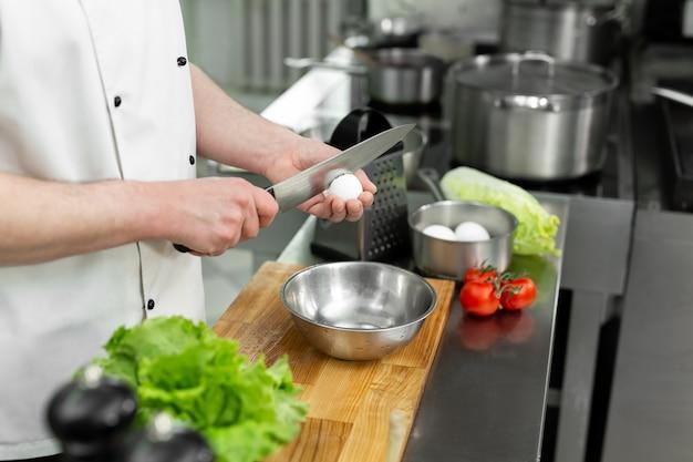 Koch bricht ein ei eigelb fällt in die schüssel