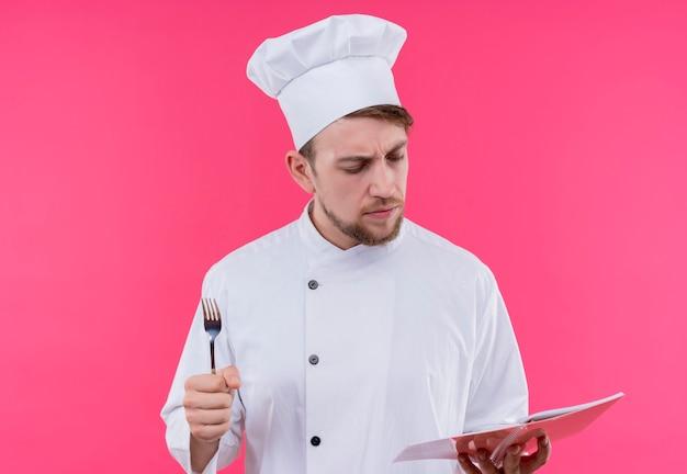 Koch, der ernsthaft schaut, um mit kreide zu buchen, die über rosa wand steht