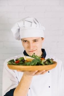 Koch, der hölzerne Platte mit Salat betrachtet