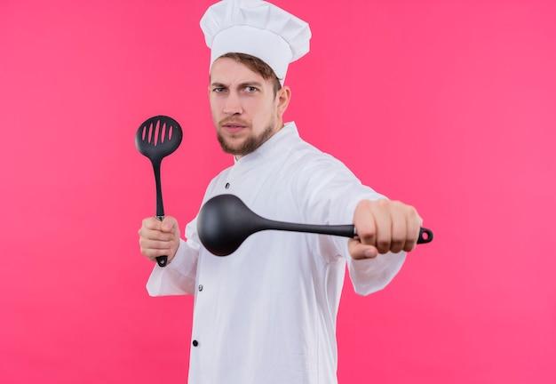 Koch, der kamera mit mutigem ausdruck wie bereit für den kampf mit löffel auf händen betrachtet, die über rosa wand stehen