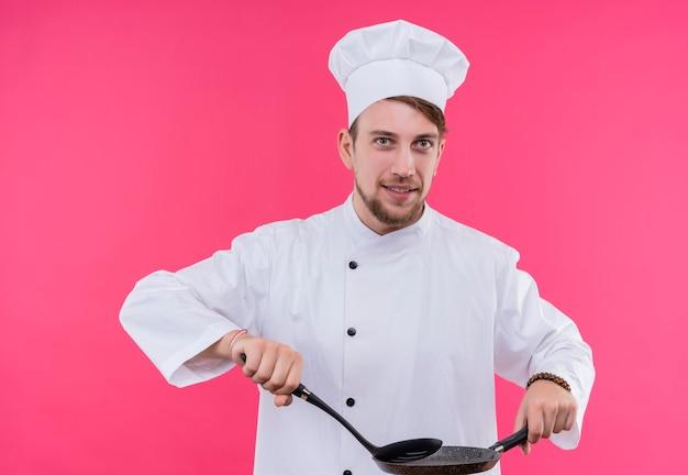 Koch, der kameralächeln auf gesicht mit löffel auf pfanne betrachtet, der über rosa wand steht