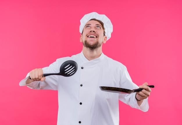 Koch, der lächeln auf gesicht mit löffel und pfanne nach oben schaut, die über rosa wand stehen