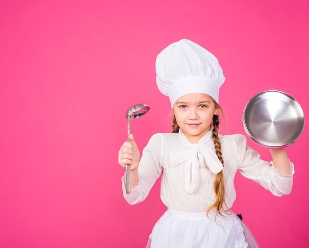 Koch des kleinen mädchens mit dem schöpflöffel- und abdeckungslächeln