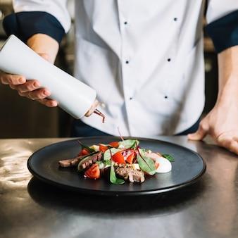 Koch gießt soße auf teller mit salat