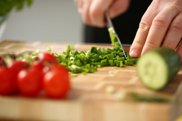 Koch hält messer in der hand und schneidet o