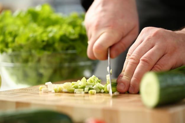 Koch hält messer in der hand und schneidet weiter