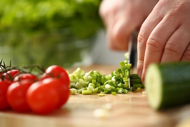 Koch hält messer in der hand und schneidet