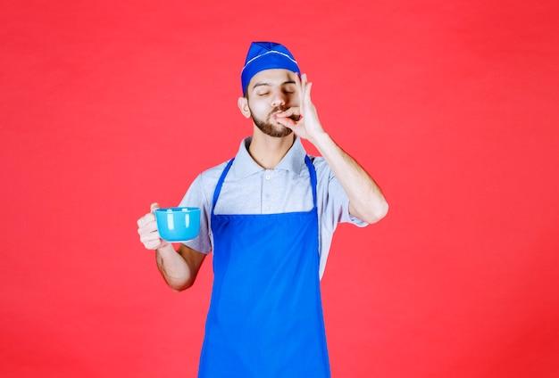 Koch in blauer schürze, die eine blaue keramiktasse hält und den geschmack des produkts genießt.