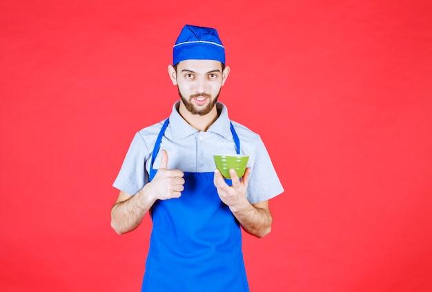 Koch in blauer schürze, die eine grüne keramiktasse hält und zufriedenheitszeichen zeigt.