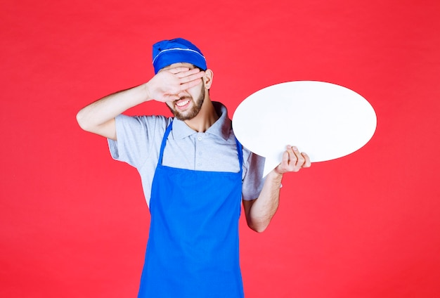 Koch in blauer schürze, die eine ovale infotafel hält und kopfschmerzen hat.