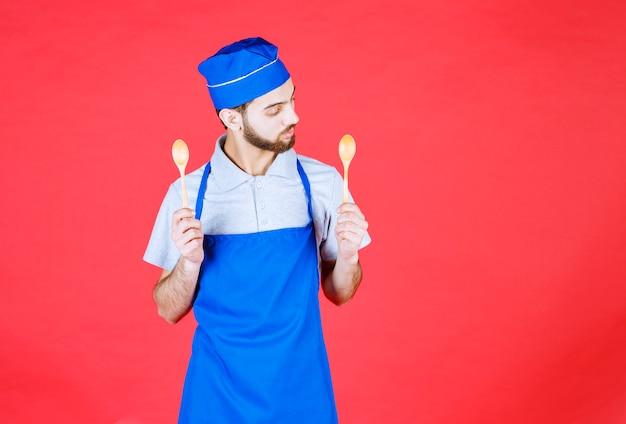 Koch in blauer schürze, die kleine holzlöffel hält und über die wahl nachdenkt.