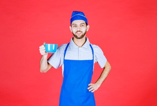 Koch in blauer schürze mit einer blauen keramikschale.