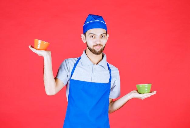 Koch in blauer schürze mit gelben und grünen keramikbechern in beiden händen.