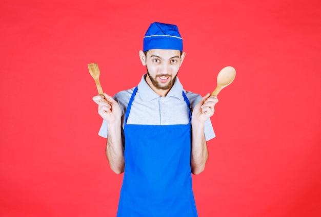 Koch in blauer schürze mit holzlöffel und spachtel.
