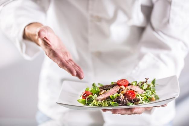 Koch in der küche des hotels oder restaurants, der das essen kurz vor dem servieren zeigt.