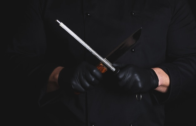Koch in schwarzen latexhandschuhen schärft ein messer