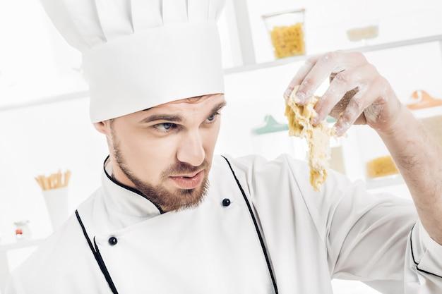 Koch in uniform macht teig in der küche. schlechter teig