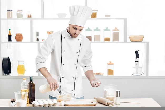 Koch in uniform macht teig in der küche