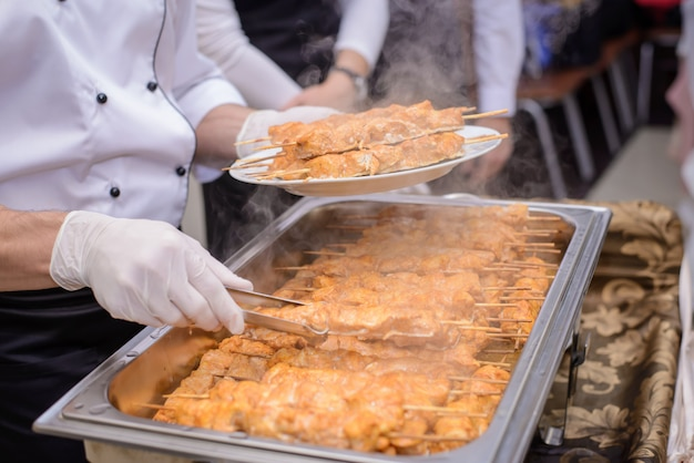 Koch legt heißes hühnerfleisch in einen teller