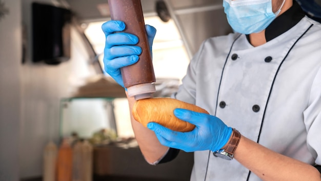 Koch machen hot dog, hinzufügen von sauce, food truck food
