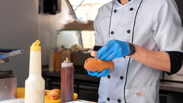 Koch macht hot dog, fügt wurst hinzu, imbisswagen