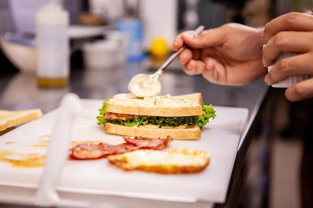 Koch macht sandwich mit frischen zutaten. leckere ernährung