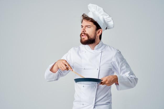 Koch mit einer bratpfanne in der hand isolierter hintergrund