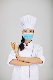 Koch mit holzgabel und spatel