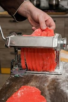 Koch mit nudelmaschine kocht roten nudelteig