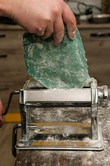 Koch mit nudelmaschine macht blauen nudelteig