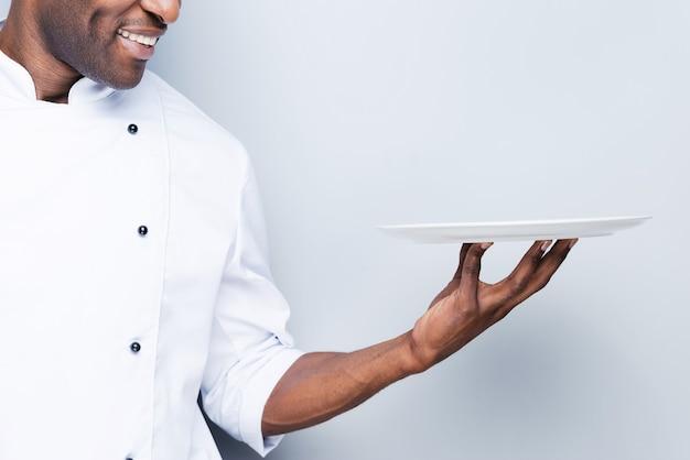 Koch mit teller. nahaufnahme eines selbstbewussten jungen afrikanischen kochs in weißer uniform mit leerem teller