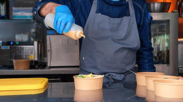 Koch, salat zubereiten, sauce hinzufügen, food truck