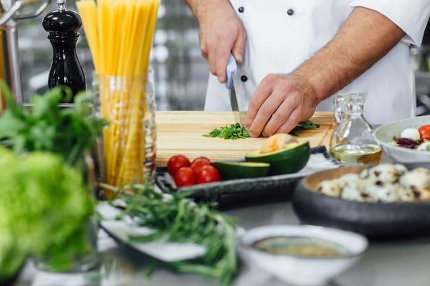 Koch schneidet das gemüse und bereitet salat zu.