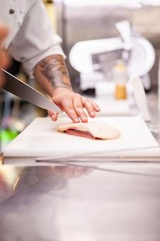 Koch schneidet entenbrust im küchenrestaurant. fleischzubereitung