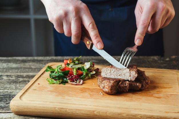 Koch schneidet gegrilltes rindersteak auf holzbrett. saftiges gegrilltes rindersteak mit gewürzen auf schneidebrett. hauptgericht rindfleisch abendessen. abendessen mit steakbeef und salat.
