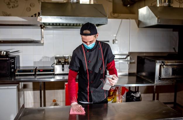 Koch trägt medizinische maske desinfektionstisch mit antiseptikum