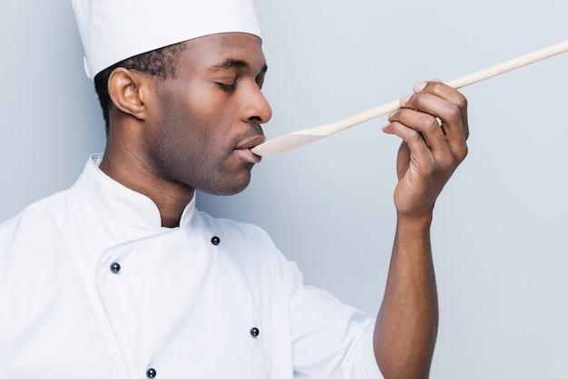 Koch versucht mahlzeit. seitenansicht eines selbstbewussten jungen afrikanischen kochs in weißer uniform, der die augen geschlossen hält