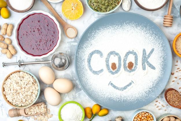 Kochaufdruck von oben auf pulverisiertem mehl auf blauem teller und anderen stoffen auf weißem tisch