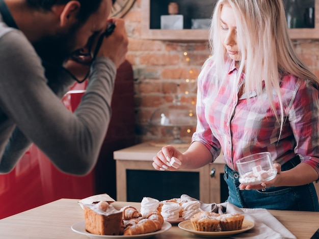 Kochblog. hobby und lifestyle. mann und frau schießen marshmallow. süße backwaren herum.