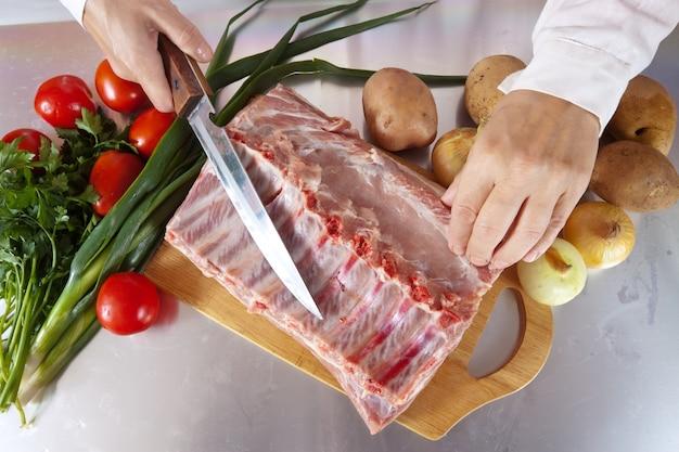 Koche hände mit rohem fleisch