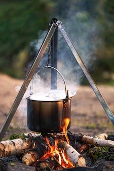 Kochen am lagerfeuer in einem kessel auf einer wanderung